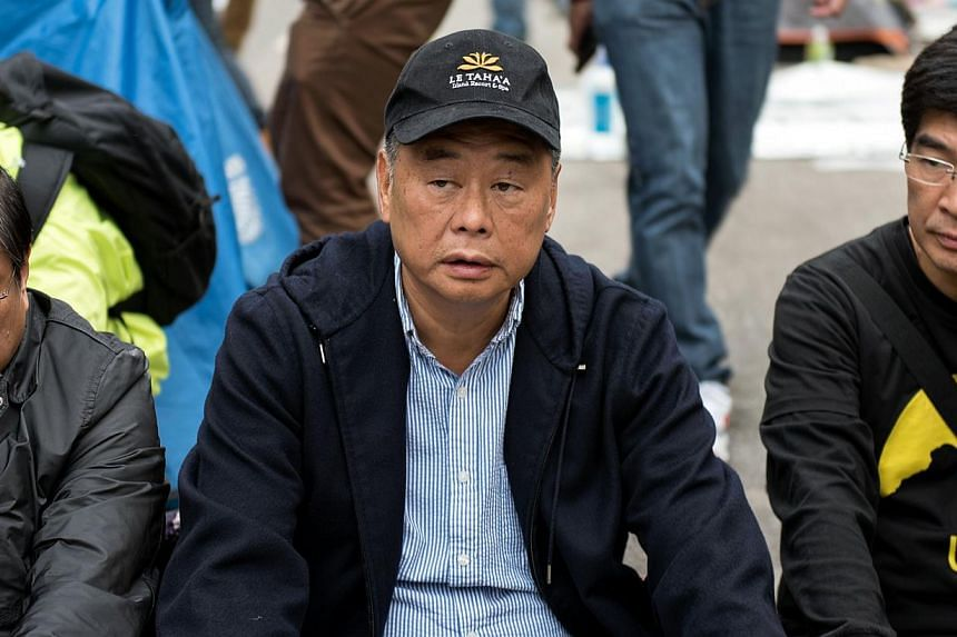 Hong Kong media tycoon Jimmy Lai (centre) sits on a blocked road at the main pro-democracy protest site in the Admiralty district of Hong Kong on Dec 11, 2014. -- PHOTO: AFP