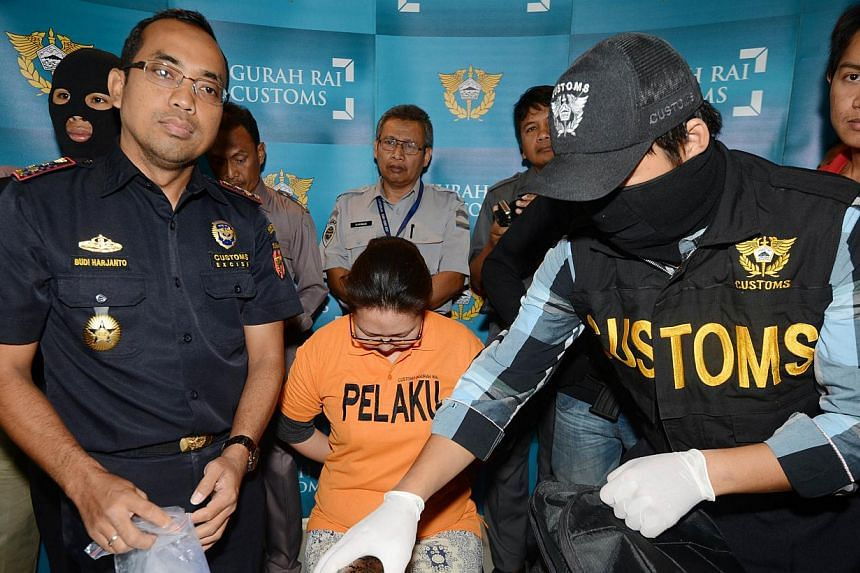 Aleksandra Magnaeva (in orange) of Russia is presented to the media by customs officials for a press conference at the customs office in Denpasar on Indonesia's resort island of Bali on Dec 11, 2014. -- PHOTO: AFP