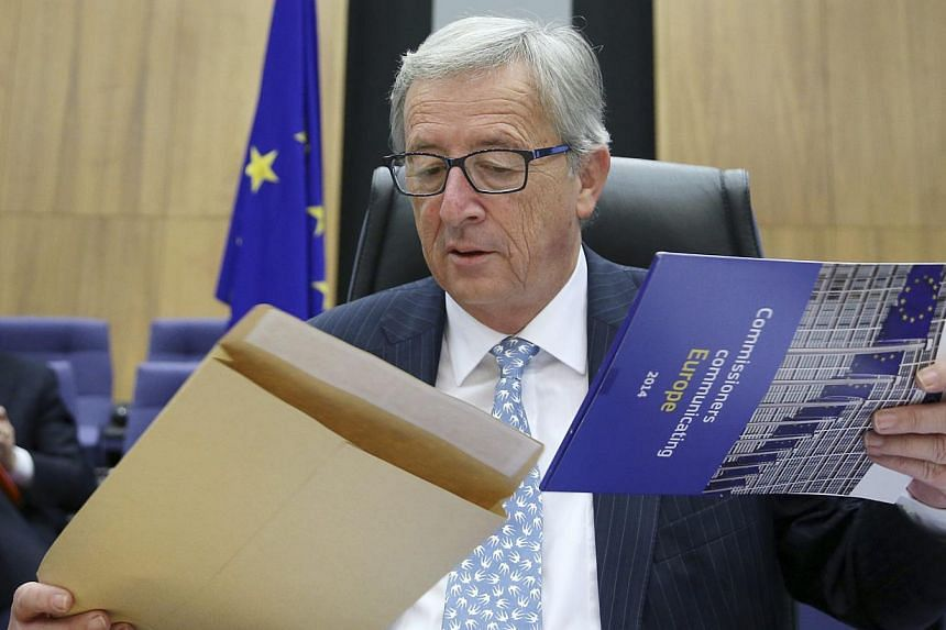 The European Commission's new President Jean-Claude Juncker opens an envelope as he chairs the first official meeting of the EU's executive body at the EU Commission headquarters in Brussels on Nov 5, 2014. -- PHOTO: REUTERS