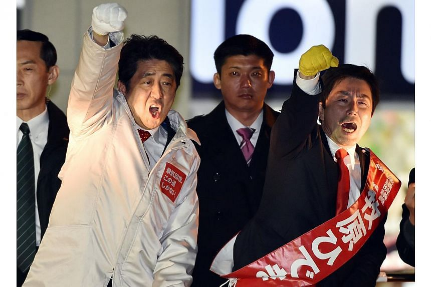 Japanese Prime Minister and ruling Liberal Democratic Party (LDP) leader Shinzo Abe (left) and his his party candidate Hideki Makihara (right). The LDP is set to sweep elections this weekend. -- PHOTO: AFP