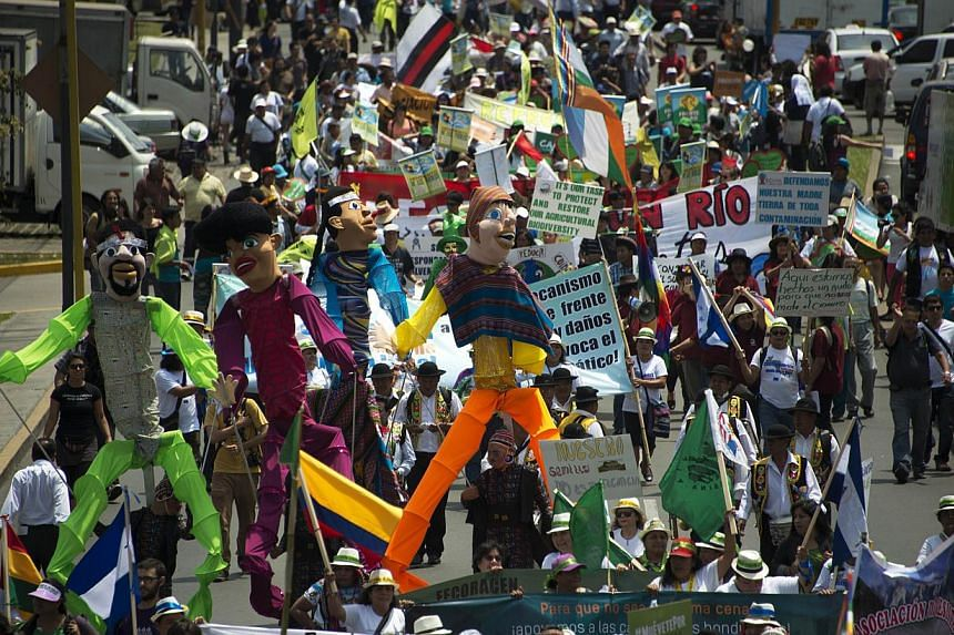 Thousands participate in the People's Climate March on the sidelines of the UN COP20 and CMP10 climate change conferences being held in Lima on Dec 10, 2014. -- PHOTO: AFP