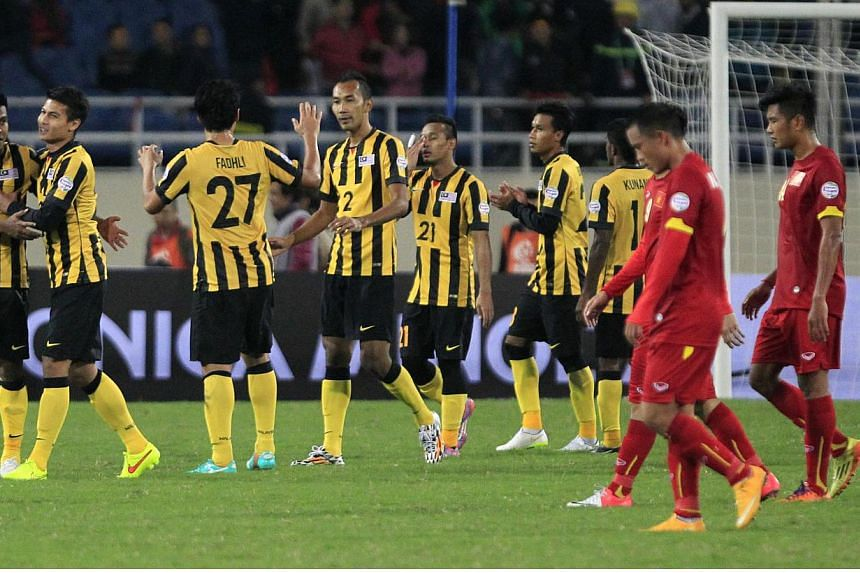 Malaysia's players (in yellow) celebrate their 4-2 victory over Vietnam after the second leg of their AFF Suzuki Cup 2014 semi-final second leg tie at the My Dinh stadium in Hanoi on Dec 11, 2014. -- PHOTO: REUTERS