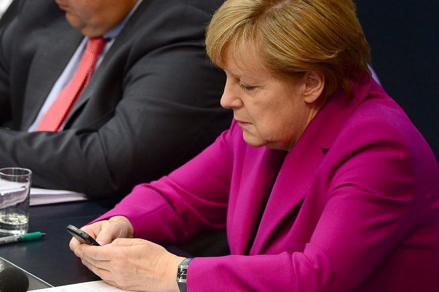 German Chancellor Angela Merkel holding her mobile phone during a session of the Bundestag Lower House of parliament in Berlin on June 4, 2014.Germany's top public prosecutor said an investigation into suspected tapping of Chancellor Angela Mer