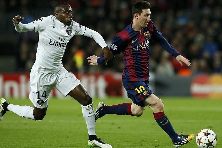 Barcelona's Lionel Messi (right) is challenged by Paris St Germain's Blaise Matuidi during their Champions League Group F soccer match at the Nou Camp stadium in Barcelona, Dec 10, 2014. Messi's goal that brought Barcelona level with Paris Saint-Germ