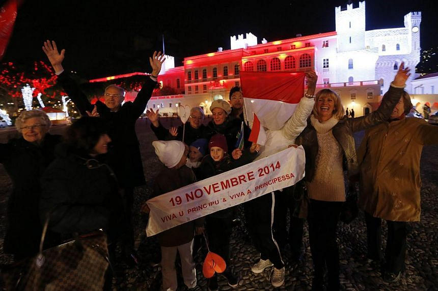People celebrate in front of the Palace of Monaco as they celebrate the birth of baby twins to Prince Albert II and Princess Charlene of Monaco on Dec 10, 2014 in Monaco. -- PHOTO: AFP