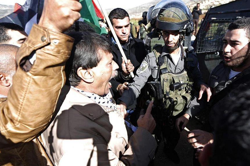 "Palestinian minister Ziad Abu Ein (centre) argues with Israeli border policemen during a protest near the West Bank city of Ramallah Dec 10, 2014. EU foreign affairs head Federica Mogherini demanded an ""immediate"" inquiry Wednesday into the death of"