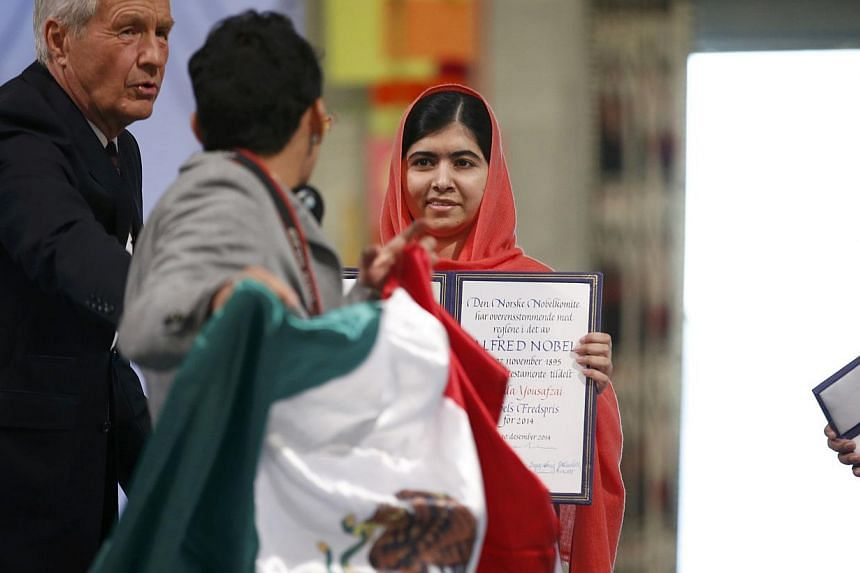 Chair of The Norwegian Nobel Committee, Thorbjorn Jagland (left) tries to stop a young man with a Mexican flag from approaching Nobel Peace Prize laureate Malala Yousafzai during the Nobel Peace Prize awards ceremony at the City Hall in Oslo Dec 10,