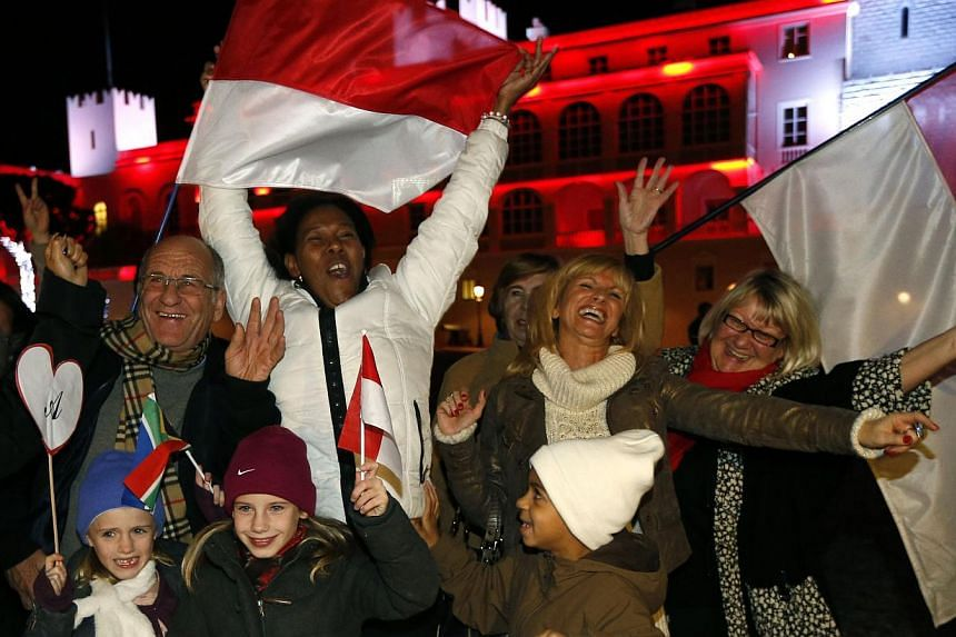 People celebrate in front of the Palace of Monaco as they celebrate the birth of baby twins to Prince Albert II and Princess Charlene of Monaco on Dec 10, 2014 in Monaco. Prince Albert II of Monaco and his wife Charlene welcomed their twin babies Gab
