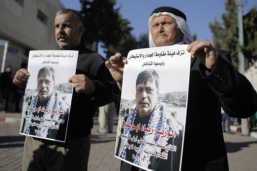 People hold posters of Palestinian minister Ziad Abu Ein at a hospital in the West Bank city of Ramallah Dec 10, 2014.Israeli Defence Minister Moshe Yaalon expressed regret for the death on Wednesday of a senior Palestinian official after a con