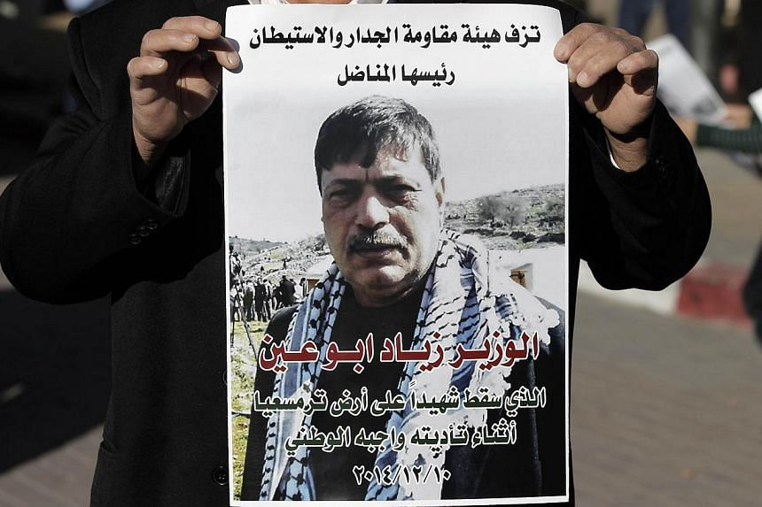 A Palestinian man carries a poster bearing the portrait of Palestinian Minister Ziad Abu Ain, after the announcement of his death outside the main hospital in the West Bank city of Ramallah on Dec 10, 2014.-- PHOTO: AFP