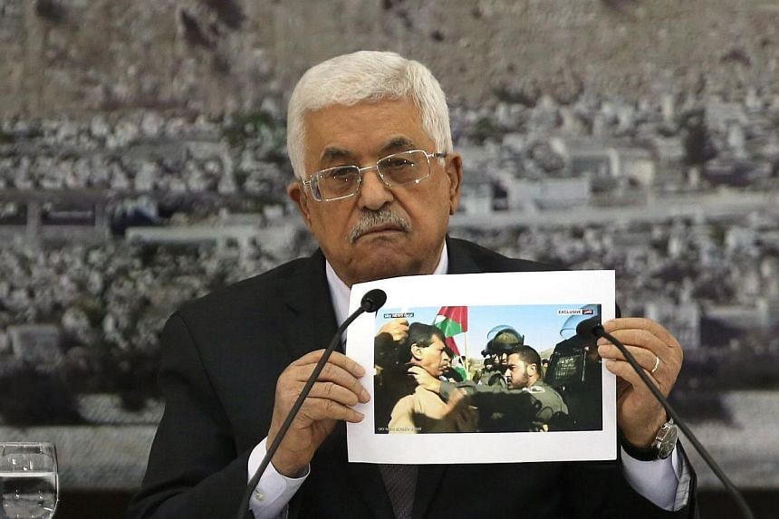 Palestinian President Mahmoud Abbas holds up a picture of senior Palestinian offical Ziad Abu Ein a in a confrontation with an Israeli security member during a leadership meeting in the West Bank city of Ramallah on Dec 10, 2014.-- PHOTO: AFP