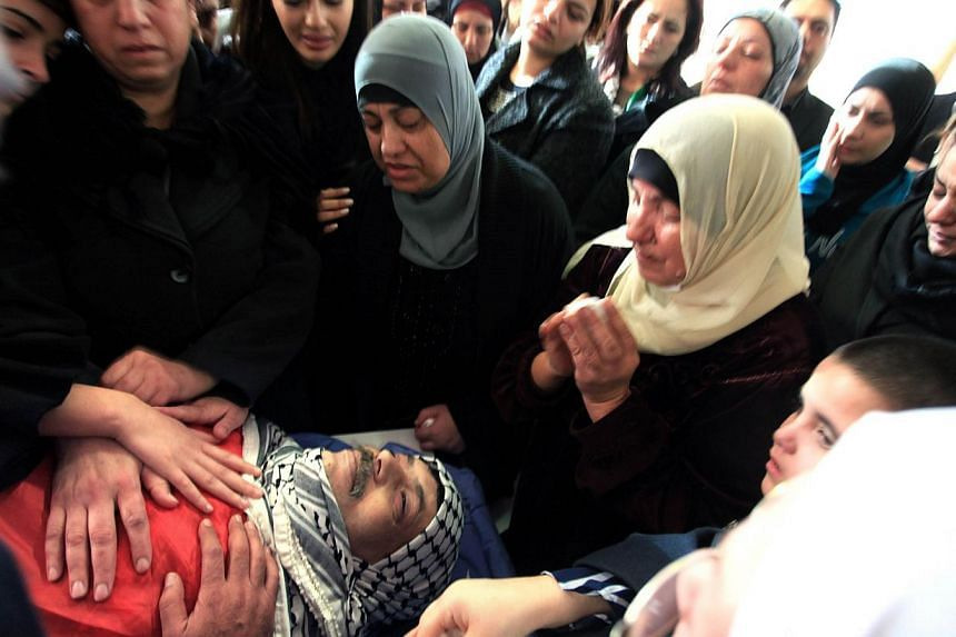 Relatives of senior Palestinian official Ziad Abu Ein mourn over his body before the funeral in the West Bank city of Ramallah on Dec 11, 2014. -- PHOTO: AFP