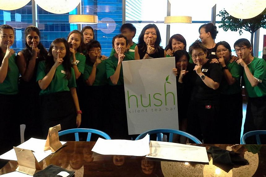Hush founder Anthea Ong (holding the Hush sign), 46, with her team. The social enterprise's deaf tea servers go to workplaces to guide executives through a tea-drinking session, in which they practise mindfulness and self-reflection. -- PHOTO