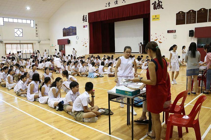 Kong Hwa School pupils collecting their PSLE results. The secondary school posting results will be released next Friday, Dec 19, the Ministry of Education (MOE) said Friday. -- PHOTO: ST FILE