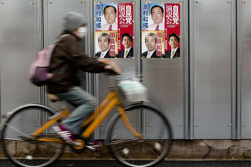 A man cycles past election posters ahead of Japan's upcoming snap election in Tokyo on Dec 11, 2014. -- PHOTO: REUTERS