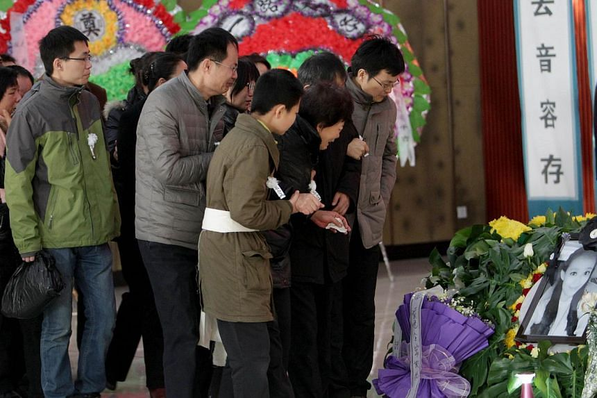 Family members and friends mourn during the funeral ceremony of Qiu Yuanyuan, a Chinese television presenter who died of cancer, in Zhengzhou, north China's Henan province on Dec 12, 2014. -- PHOTO: AFP