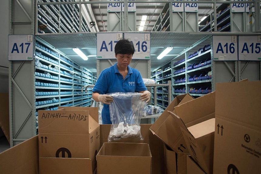 This picture taken on Sept 24, 2014, shows workers packing goods at a warehouse of TSLP at the China (Shanghai) Pilot Free Trade zone during a media trip. China is to launch three pilot free trade zones (FTZ) in the government's push for greater