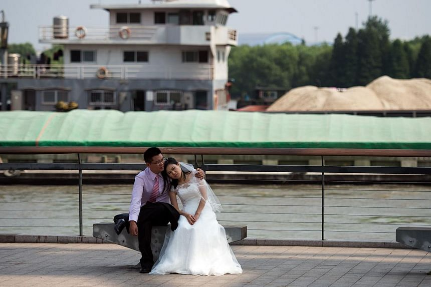 A Chinese couple takes a break during a wedding photo shoot at the West Bund in Shanghai on Sept 25, 2014.China's national anthem can no longer be performed at weddings, funerals, balls or other non-political functions and should only be