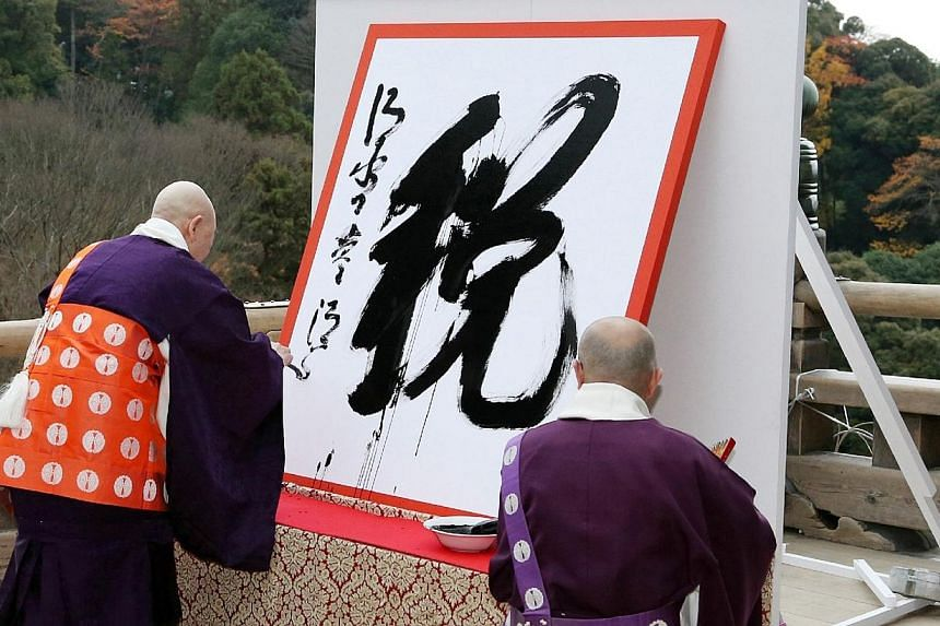 """Seihan Mori (left), the chief priest of Kiyomizu temple, displays his caligraphy of a kanji (or Chinese character),""""zei"""" meaning tax which was chosen as the single best Chinese character symbolizing this year's national ethos in Japan at the Buddhist"""