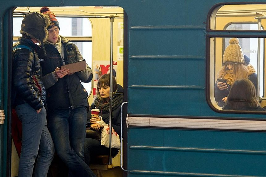 Commuters consulting their electronic connected devices inside a train coach in the Moscow Metro on Dec 1, 2014.Moscow's metro said on Friday it was carrying out emergency checks of its system after a young couple made their way into a tunnel a