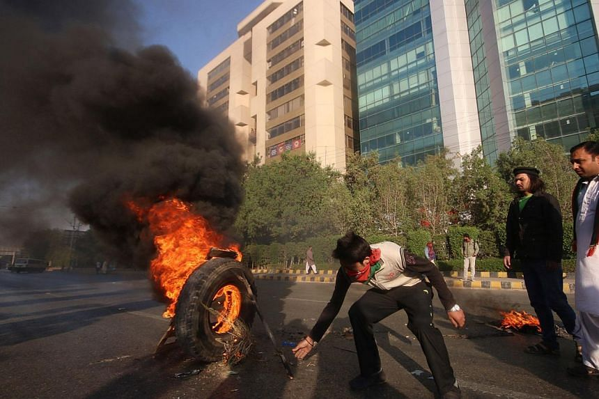 Activists of Imran Khan's Pakistan Tehreek-e-Insaaf (PTI) party burn tyres on a street during a protest in Karachi on Dec 12, 2014. The latest round of protests against the Pakistani government led by cricketer-turned-politician Imran Khan disru