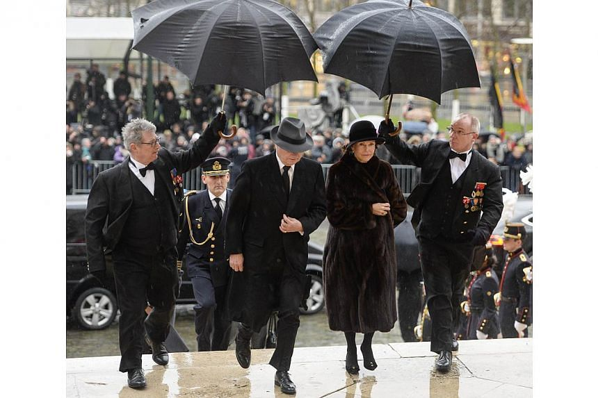 Carl XVI Gustaf of Sweden and Queen Silvia of Sweden arrive at the Saint Michael and Saint Gudula cathedral in Brussels, on Dec 12, 2014, for the funeral of late Queen Fabiola of Begium. -- PHOTO: AFP/BELGA