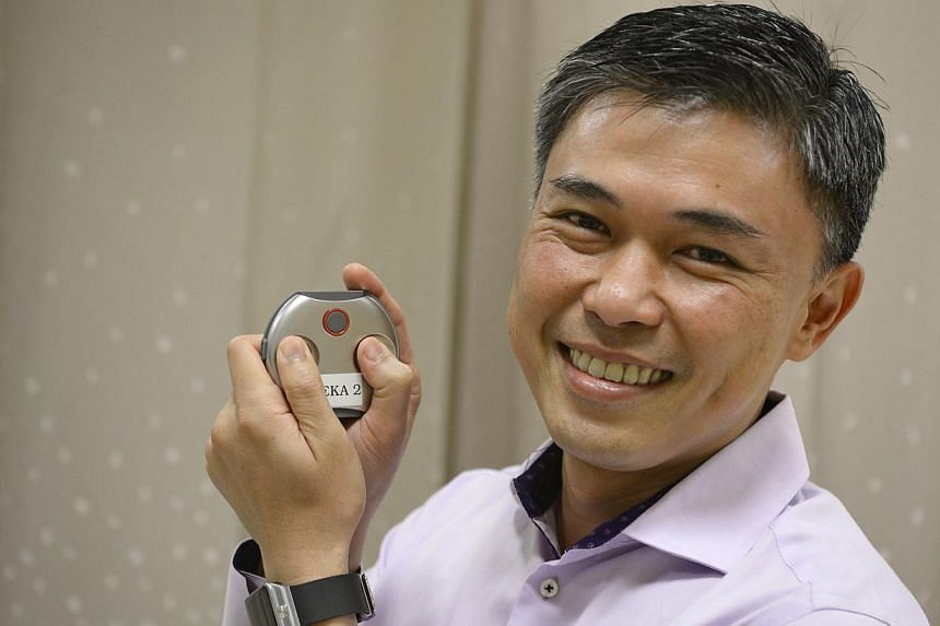 The Reka medical device in cardiologist Lim Toon Wei's hands allows patients to be monitored for longer periods.