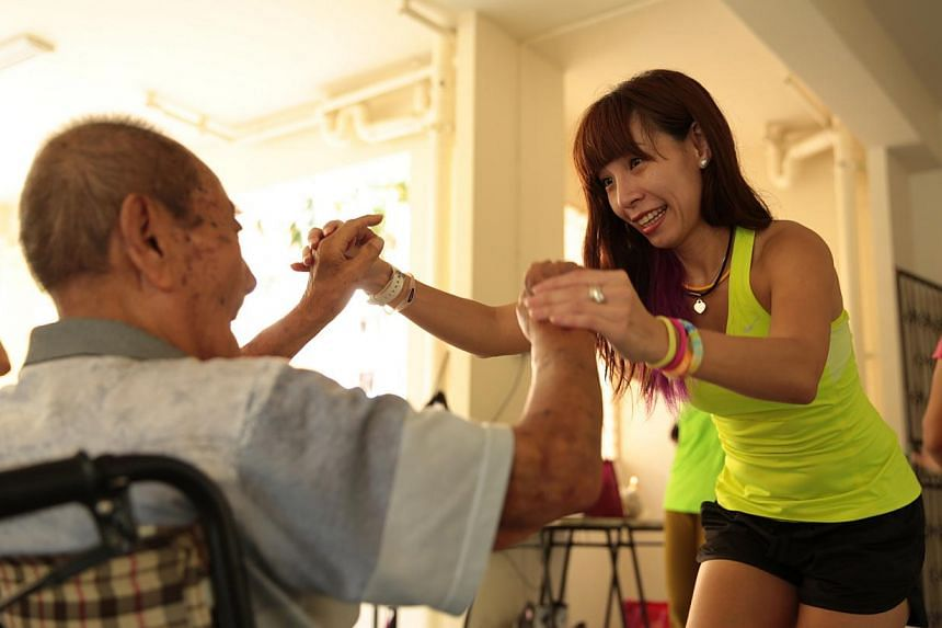 Volunteer Cyndi Chua with an elderly resident at a fitness class at the Thye Hua Kwan Seniors Activity Centre. Get Movin' for Charity conducts free zumba and fitness classes for seniors.