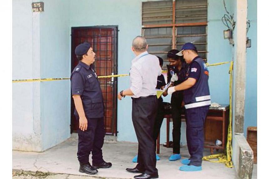 Police investigators outside the longhouse unit in Kampung Pisang in the Machang Bubok area on mainland Penang where Myanmar nationals were murdered and dismembered in brutal killings. -- PHOTO: NSTP