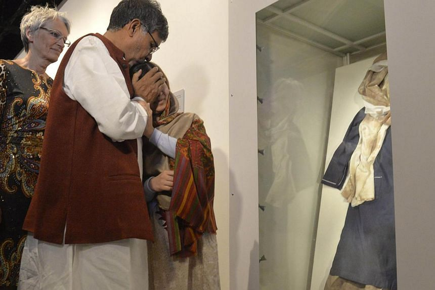 Nobel Peace Prize winners Kailash Satyarthi and Malala Yousafzai with Malala's bloodstained school uniform at the opening of the Nobel Peace Prize exhibition at the Nobel Peace Centre on Dec 11, 2014. -- PHOTO: AFP