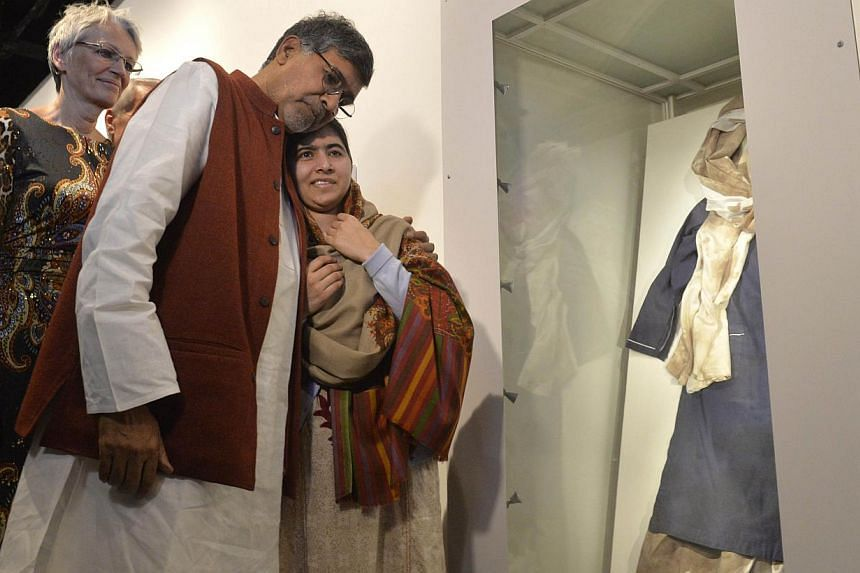 Nobel Peace Prize winners Kailash Satyarthi and Malala Yousafzai with Malala´s bloodstained school uniform at the opening of the Nobel Peace Prize exhibition at the Nobel Peace Centre on Dec 11, 2014. -- PHOTO: AFP