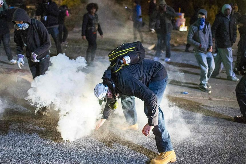 A demonstrator reaches for a tear gas canister during a protest in the St Louis suburb of Ferguson, Missouri on Nov 25, 2014. A federal judge on Thursday ordered St Louis police to issue warnings before firing tear gas, following complaints by activi