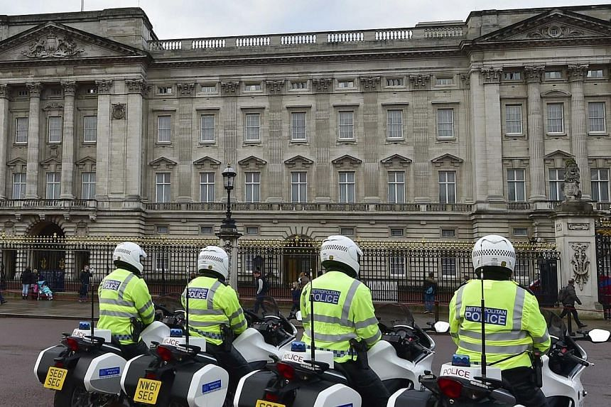 Police motorcycle outriders wait outside Buckingham Palace in central London, Oct 24, 2014.A species of hallucinogenic mushroom has been found growing wild in the grounds of Buckingham Palace, the main residence of Britain's Queen Elizabeth. --