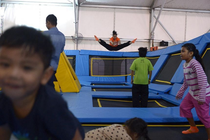 Nazyra Suhairi (centre), a 22-year-old fresh graduate, jumps on trampolines at the main court at the newly opened Zoom Park on Dec 13, 2014. -- ST PHOTO: MARK CHEONG
