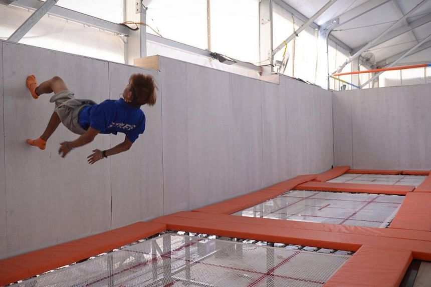 Parkour practitioner and full-time NSF Muhd Zaki Zakwan, 20, walks up a wall after bouncing up from the high performance trampoline area at the newly opened Zoom Park on Dec 13, 2014. -- ST PHOTO: MARK CHEONG