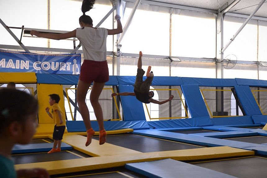 Visitors jump on trampolines at the main court at the newly opened Zoom Park on Dec 13, 2014. -- ST PHOTO: MARK CHEONG