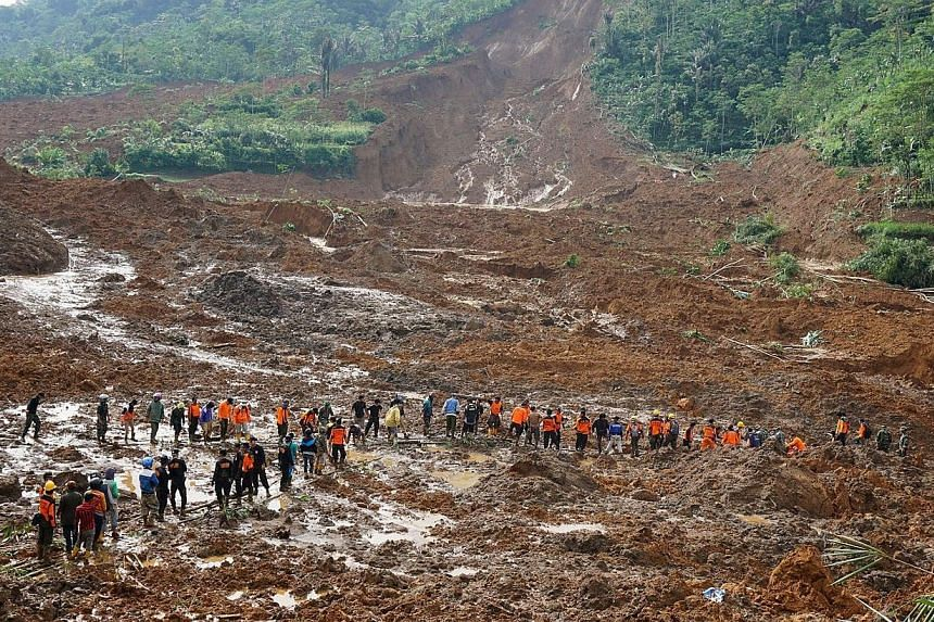 A rescue team remove victims bodies of a landslide triggered by torrential downpours at Jemblung village in Banjarnegara, Central Java province on Saturday, Dec 13, 2014.At least 17 people were killed and nearly 100 others left missing in the l