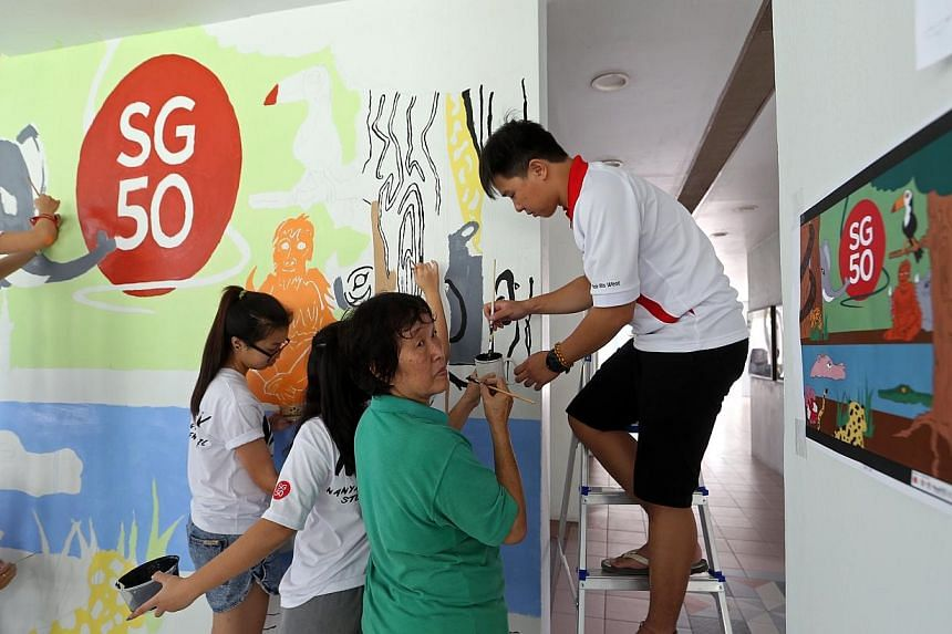 Pasir Ris West resident Mdm Pang Ah Choon, 65, referring to a printout of an artwork while painting a wall mural at the void deck of Blk 537 Pasir Ris St 51. She is among about 800 residents and students from Nanyang Polytechnic painting wall murals