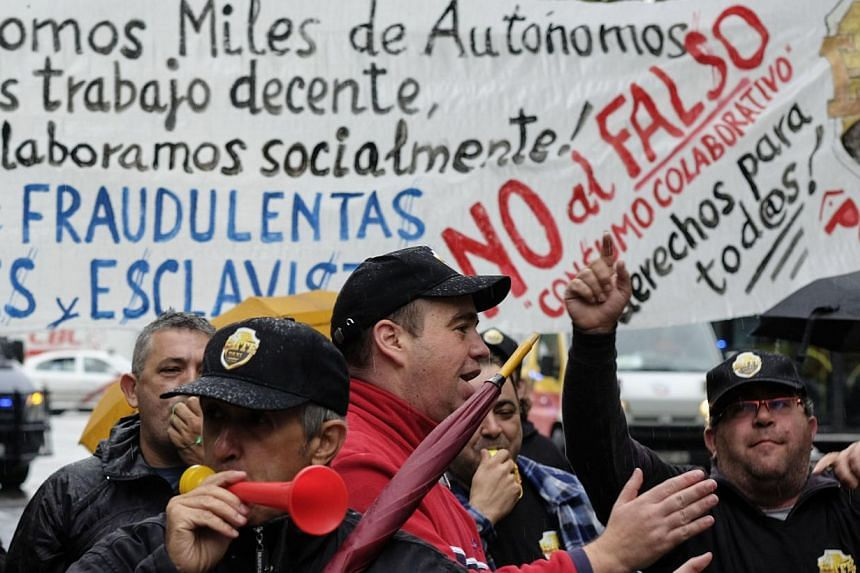 A protest by taxi drivers against Uber in Madrid in October. Most nations have rules to introduce a taxi service, but Uber's standard operating formula is to argue that no laws apply to the company.