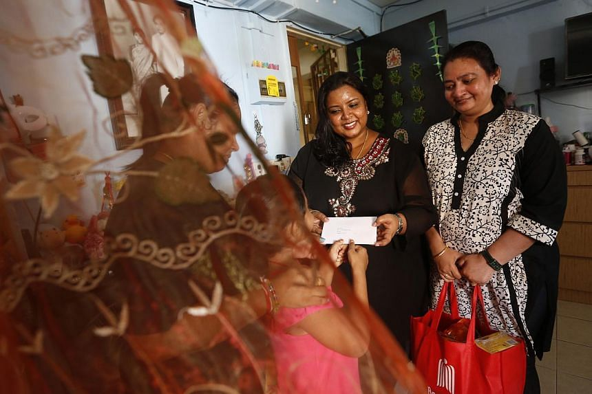 Volunteers (from right) J. Rubyrani and Sakuntala Jackson handing a letter from an inmate to his wife, Madam Eswari Vadivel, and daughter, together with a food hamper. The Angel Tree Project has had letters hand-delivered to inmates' families in the