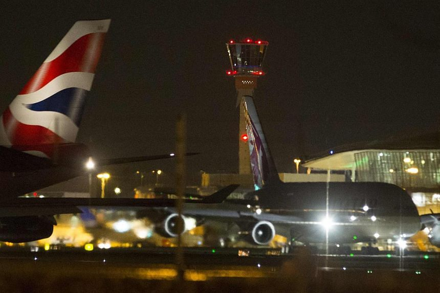 Aircraft taxi next to the control tower at Heathrow airport in London on Dec 12, 2014. -- PHOTO: REUTERS