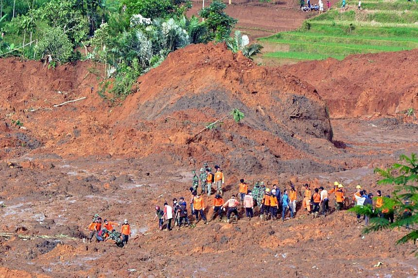 A rescue team searches for survivors and remove bodies after a landslide at Jemblung village in Banjarnegara, Central Java province on Dec 13, 2014. -- PHOTO: AFP