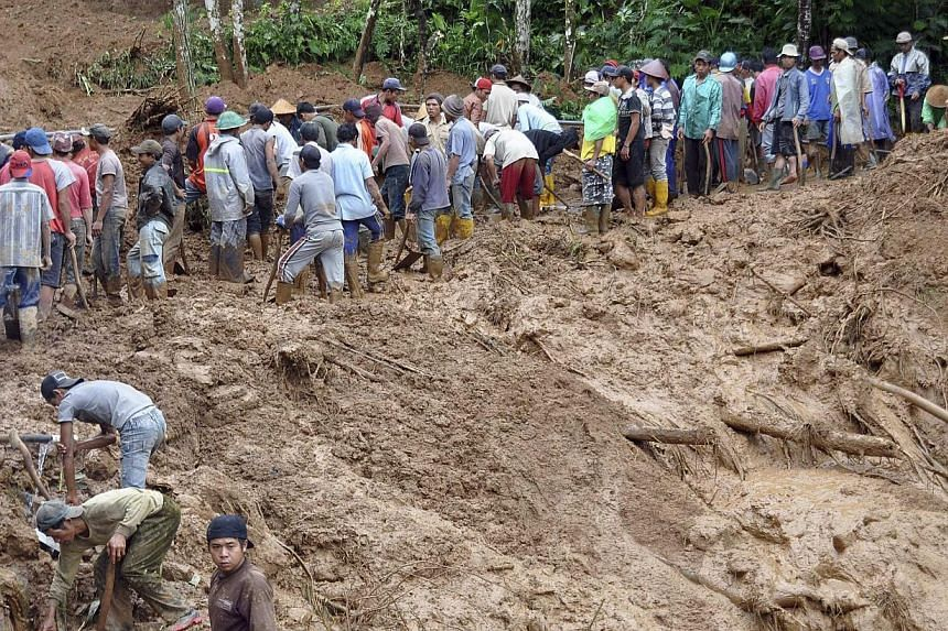 Villagers using shovels to remove mud from the main road at Pasuruhan village in Wonosobo Dec 12, 2014, in this photo taken by Antara Foto. Heavy rain caused a landslide early Friday in Pasuruhan village, with a citizen killed when a 50m-high cliff h