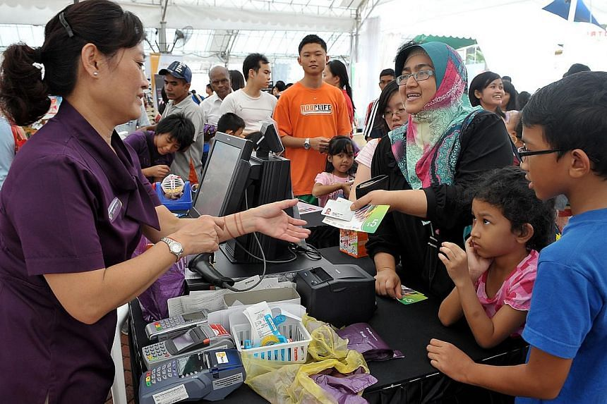 Beneficiaries receiving voucher assistance from NTUC's U Care Fund in 2011. -- PHOTO: BERITA HARIAN