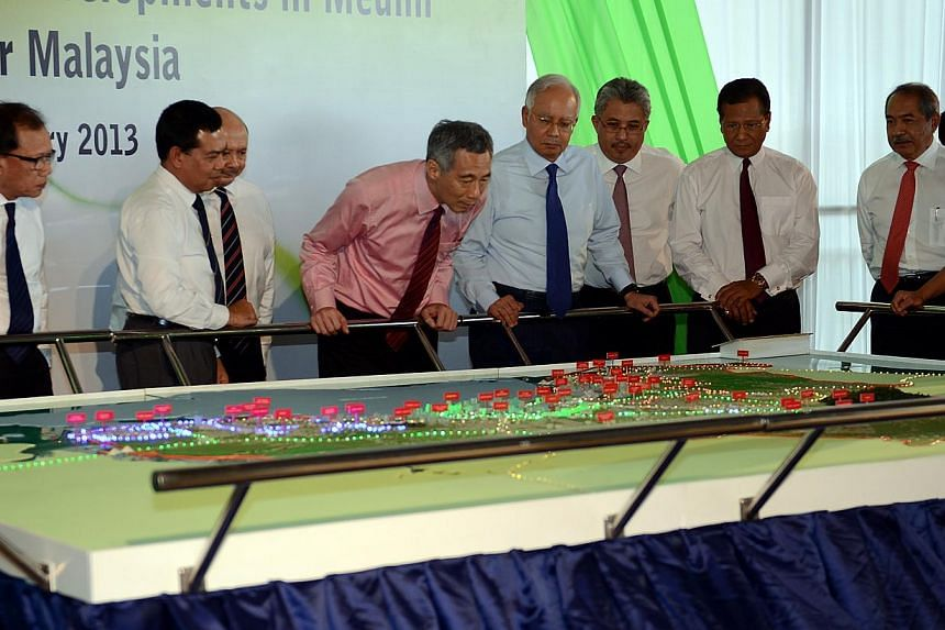 Singapore Prime Minister Lee Hsien loong (in pink) and his Malaysian counterpart Datuk Seri Najib Tun Razak (fourth from right) looking at a model of the Medini Integrated Wellness Capital in Nusajaya, Iskandar Malaysia in this file picture. A high-s