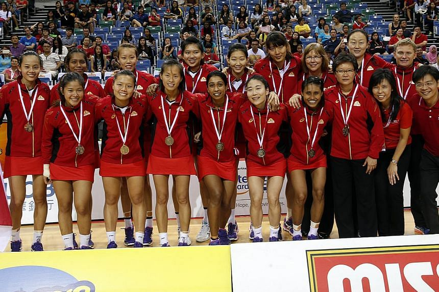 The Singapore netball team, who clinched silver at the Netball Nations Cup 2014 at the OCBC Arena yesterday, after their 50-41 loss to Samoa in the final.-- ST PHOTO:LAU FOOK KONG