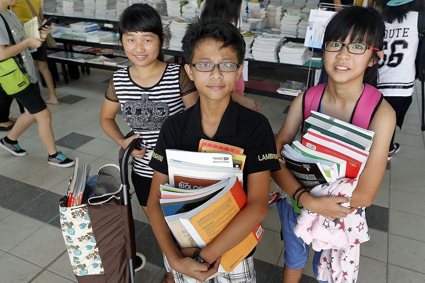 Xavier Kok Tong Shane, 13 (centre) and his sister Valerie Chan Yan Yi, (12) right were at the distribution centre, Changkat Changi Secondary School. With them is caregiver, Than Hniang Mawi, 25 (left). A record 400,000 textbooks, collected for the Fa