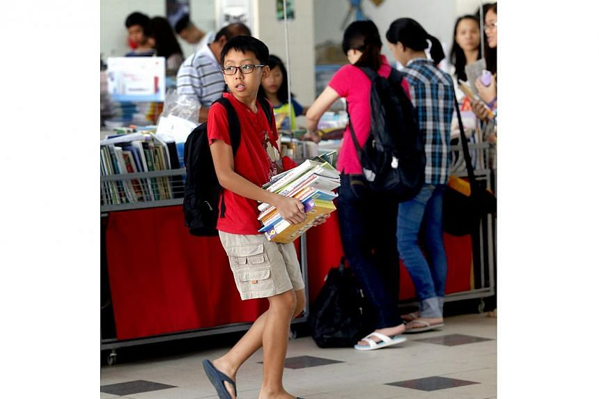 A record 400,000 textbooks, collected for the FairPrice Share-A-Textbook Project, were given out free to needy students on Dec 13.-- ST PHOTO: CHEW SENG KIM