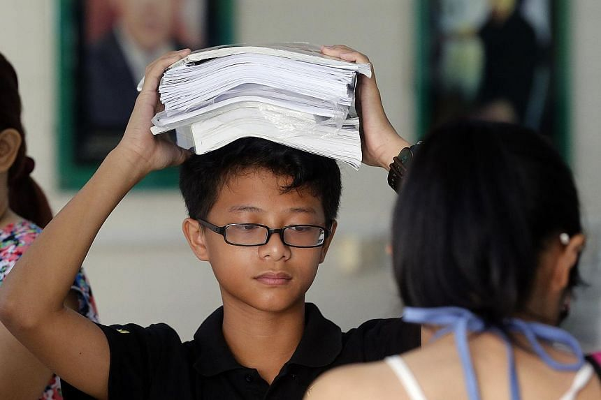 Xavier Kok Tong Shane, 13 at the distribution centre, Changkat Changi secondary School with books on his head. A record 400,000 textbooks, collected for the FairPrice Share-A-Textbook Project, were given out free to needy students on Dec 13. -- ST PH