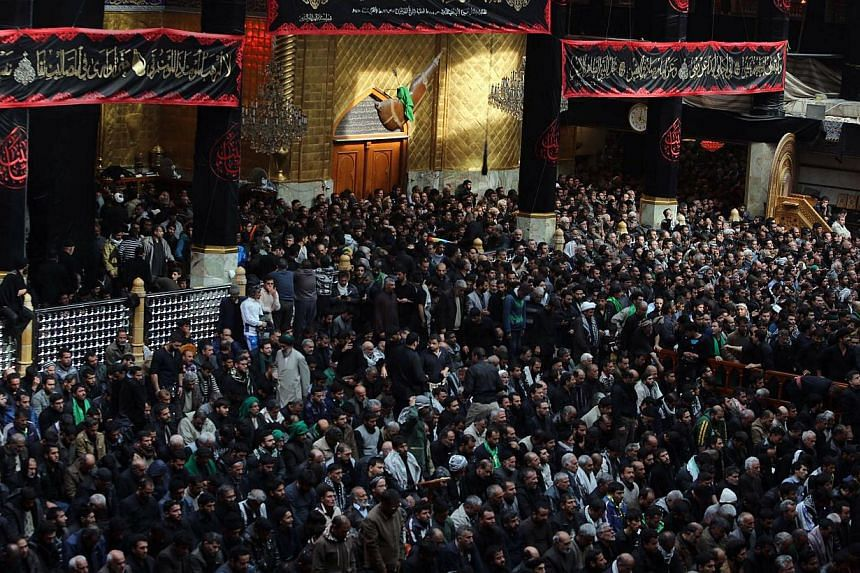 Iraqi Shi'ite Muslim pilgrims take part in Friday prayers at the shrine of Imam Abbas in Karbala on Dec 12, 2014.Millions of Shi'ite Muslim pilgrims defied the threat of extremist attacks and thronged the Iraqi shrine city for the climax of the